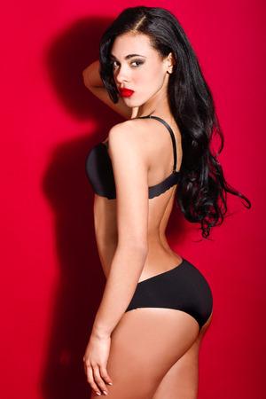 Red panties: Latin woman wearing black bra and panties on red . Studio shot.