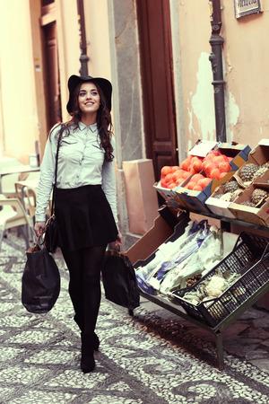 denim skirt: Young woman with shopping bags walking near a fruits shop. Wearing skirt, shirt and hat.