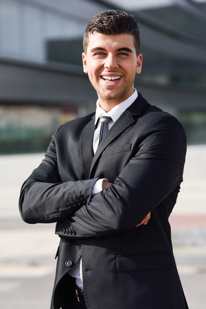 hair tie: Young businessman near a modern office building wearing black suit and tie. Man with blue eyes smiling.