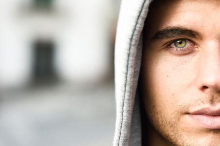 urban: Good looking young man with blue eyes in the street wearing hooded jacket
