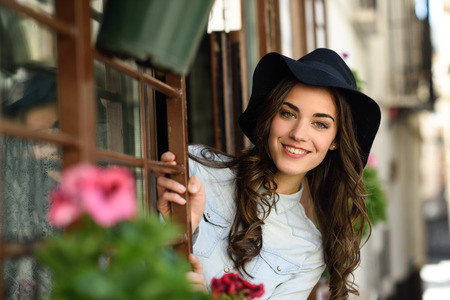 denim skirt: Portrait of young woman smiling in urban background wearing casual clothes and hat reflected in a cafe window
