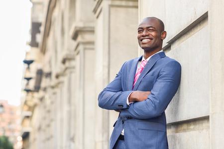 Portrait of handsome black man wearing suit, smiling in urban background