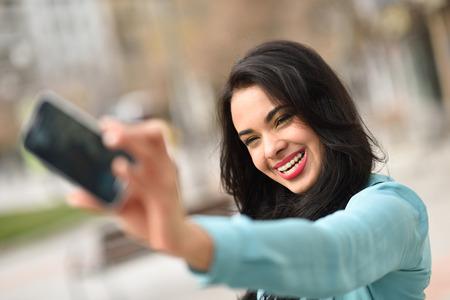 美しい若い女性は、中かっこを使用してスマート フォンでストリートで selfie の肖像画