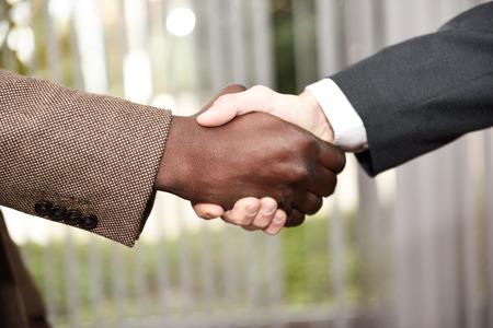 黒のビジネスマンがオフィスで白人 1 つ身に着けているスーツと握手します。クローズ アップ ショット