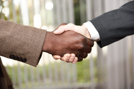 Black businessman shaking hands with a caucasian one wearing suit in a office. Close-up shot Archivio Fotografico