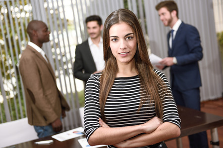 Working Environment: Businesswoman leader looking at camera with arms crossed in working environment. Group of people in the background Stock Photo