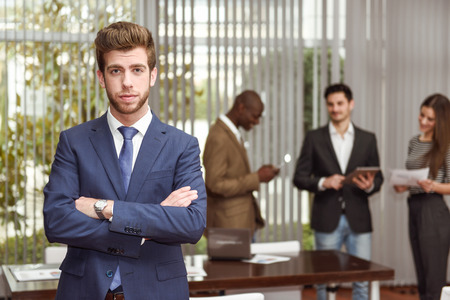group leader: Businessman leader looking at camera with arms crossed in working environment. Group of people in the background