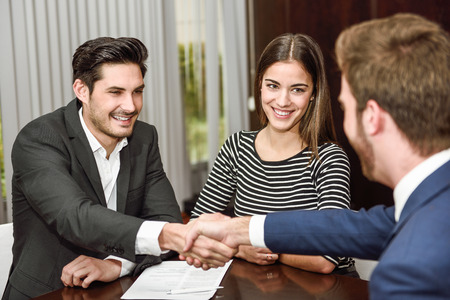 satisfied customer: Smiling young couple shaking hands with an insurance agent or investment adviser