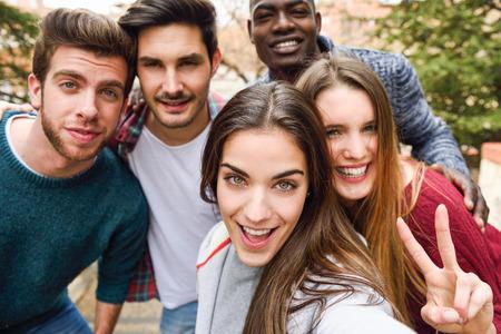 hogescholen: Groep van multi-etnische jonge mensen die plezier samen buitenshuis