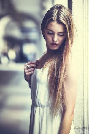 Portrait of beautiful blonde girl in urban background wearing white dress in urban background