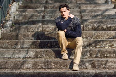 sueter: Retrato de un hombre hermoso joven, modelo de moda, con el peinado moderno sentado en las escaleras, con ropa casual.