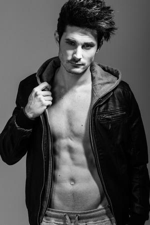 hombre sin camisa: Retrato de hombre atlético vistiendo chaqueta de la sudadera con capucha. Tiro del estudio