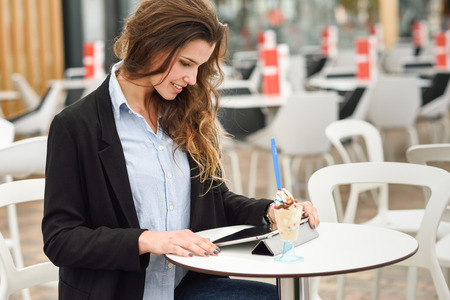Portrait of a woman looking at her tablet computer, smiling and sitting in a coffee shop photo