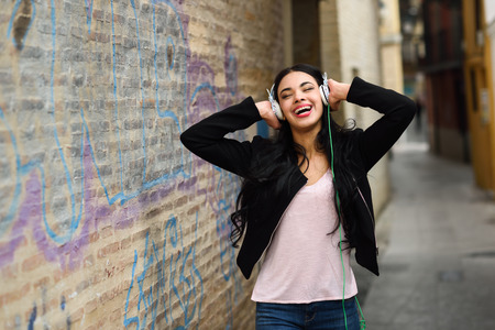 Portrait of young dominican woman in urban background listening to music with headphones photo