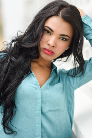 Portrait of hispanic young woman wearing casual clothes in urban background