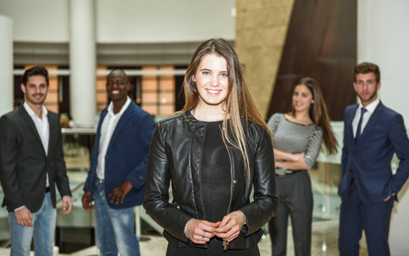 group leader: Blonde businesswoman leader looking at camera in office building. Group of multi-ethnic people in the background Stock Photo