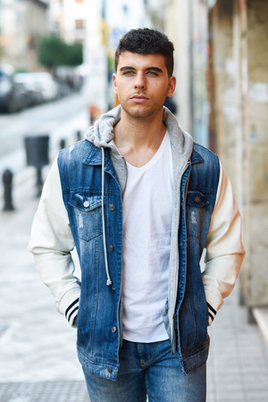 Good looking young man with blue eyes in the street. Model of fashion in urban background wearing white t-shirt, jeans and blue jacket Stock Photo
