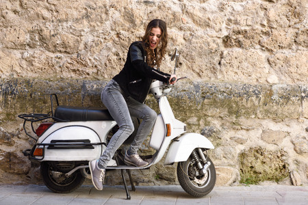 Woman launching a old scooter with pedal wearing casual clothes in urban background.
