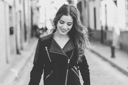 長い巻き毛のカジュアルな服を着て都市背景で笑顔の若い女性の肖像画