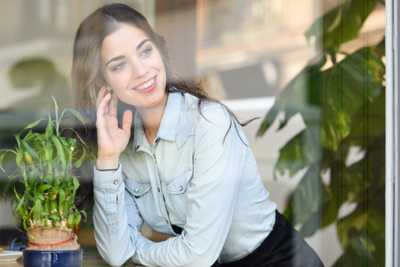 Cafe city lifestyle. Young woman smiling indoor in trendy urban cafe looking through the window. Cool young modern caucasian female model in her 20s photo