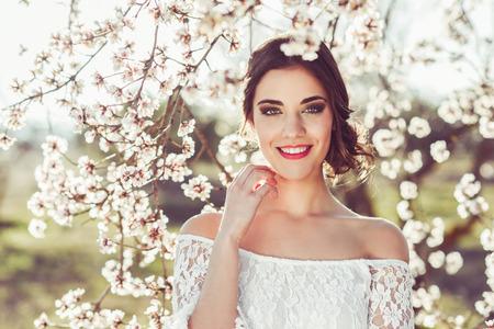 春に花が咲く庭園で笑顔の若い女性の肖像画。アーモンドを花しますの花。花嫁のような白い服を着ての女の子。 写真素材