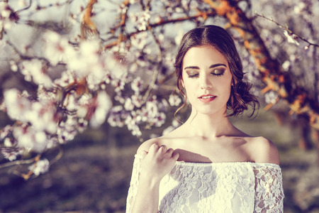 bridal hair: Portrait of young woman in the flowered garden in the spring time. Almond flowers blossoms. Girl dressed in white like a bride.