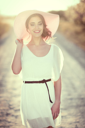 pink hat: Portrait of young woman with eyes closed in a rural road in the spring time. Girl wearing white dress, brown belt and pink sun hat. Backlight photography with the Sun in the back of the woman. Stock Photo