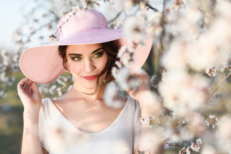 pink hat: Portrait of young woman in the flowered field in the spring time. Almond flowers blossoms. Girl wearing white dress and pink sun hat