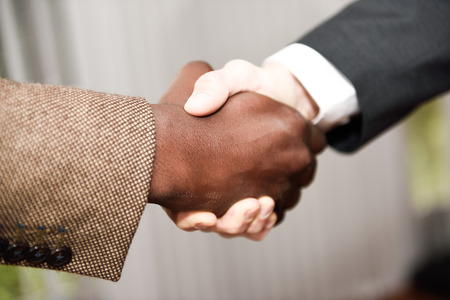 Black businessman shaking hands with a caucasian one wearing suit in a office. Close-up shot photo