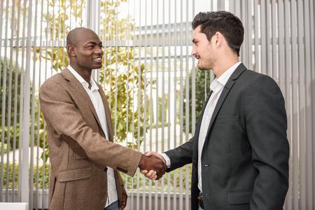 검은 사업가 사무실에서 양복을 입고 백인 하나와 악수. 웃는 두 남자