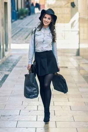 denim skirt: Beautiful brunette young woman wearing short skirt and denim shirt walking on the street with shopping bags