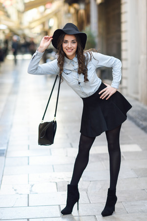 denim skirt: Portrait of young woman in urban background wearing casual clothes and hat  carrying a bag