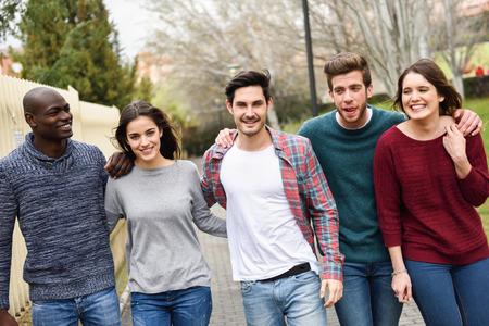 도시 배경에서 함께 야외 재미 다민족 젊은 사람들의 그룹입니다. 함께 걷는 사람의 그룹 스톡 콘텐츠