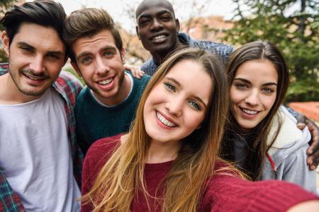 Groupe multi-ethnique d'amis prenant selfie dans un parc urbain avec une jeune fille blonde au premier plan