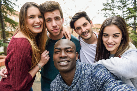 group picture: Multiracial group of friends taking selfie in a urban park with a black man in foreground