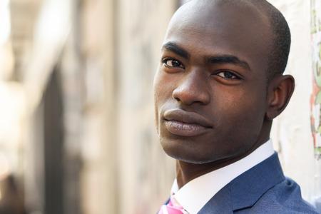 도시 배경에서 양복을 입고 잘 생긴 흑인 남자의 초상화