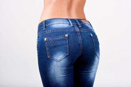 sexy latina: Woman wearing blue jeans with a beautiful waist. Studio shot Stock Photo