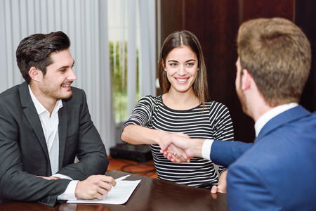 advising: Smiling young couple shaking hands with an insurance agent or investment adviser