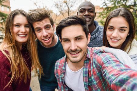 Groep van multi-etnische jongeren plezier buitenshuis samen in stedelijke achtergrond