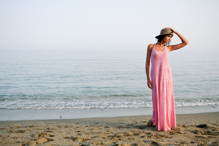 sun hat: Portrait of a beautiful woman with long pink dress and sun hat on a tropical beach Stock Photo