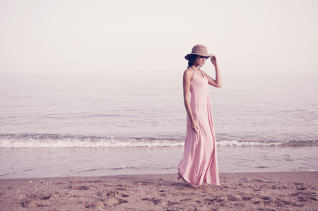 Retrato de una hermosa mujer con vestido largo de color rosa y sombrero para el sol en una playa tropical