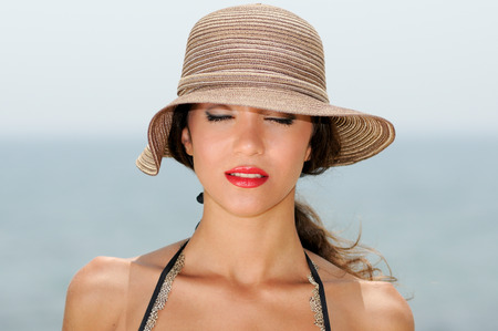 close up eyes: Close up portrait of an beautiful woman wearing sun hat on a tropical beach with her eyes closed Stock Photo