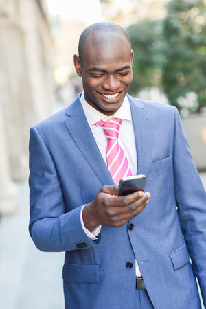 black businessman: Portrait of a black businessman wearing suit reading his smart phone in urban background