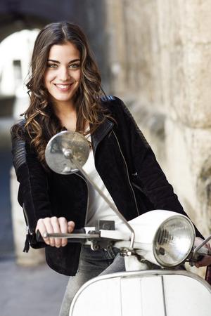 笑みを浮かべて、背景で古いスクーターでカジュアルな服を着て都市背景の女性