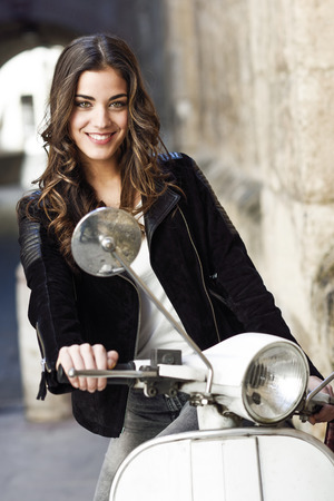 Woman in urban background smiling and wearing casual clothes with a old scooter in the background