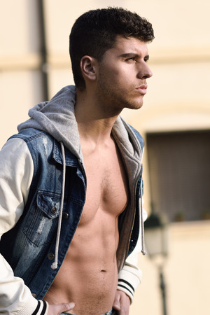 good looking model: Good looking young man with muscular body in the street. Model of fashion in urban background wearing jeans and blue jacket