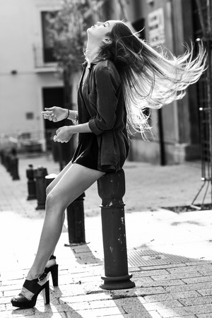 urban fashion: Portrait of blonde girl moving her amazing long hair Stock Photo