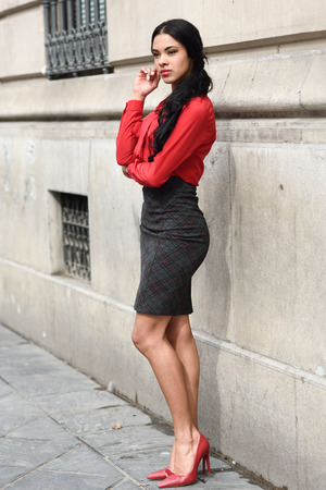 Portrait of hispanic bussinesswoman in urban background wearing red shirt and skirt