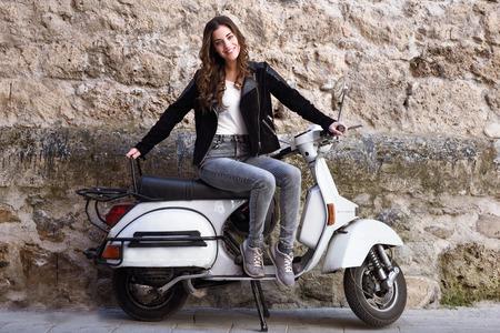 Jonge vrouw in de stedelijke achtergrond vrouw klimmen op een scooter motorfiets dragen casual kleding
