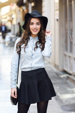 Portret młodej kobiety w tle miejskich na sobie ubrania dorywcza i kapelusz torbę